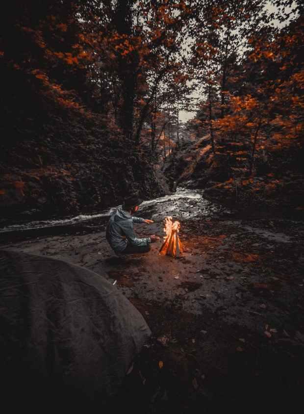 man wearing grey hoded jacket beside bonfire