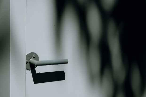 grayscale photo of gray door lever and white door panel